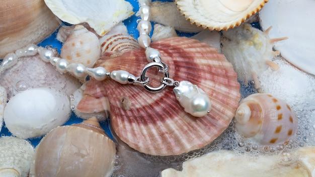 Collana di perle barocche bianche con pendente su sfondo di conchiglia marina. primo piano