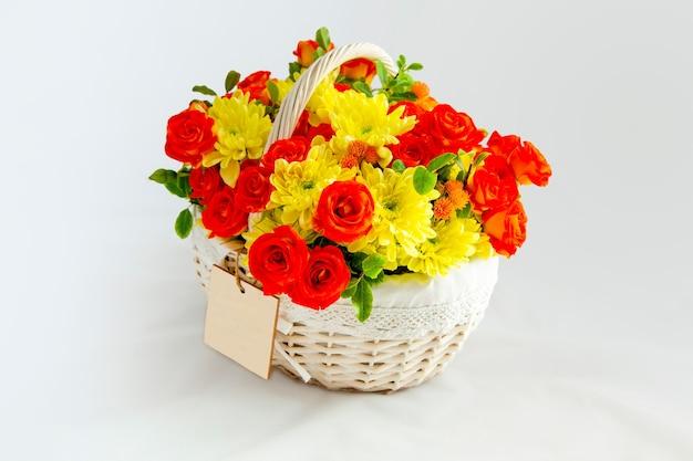 Cestino bianco con rose scarlatte e crisantemi gialli sfondo bianco per tagliare la carta in bianco
