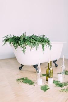 Bagno bianco decorato con felci e candele
