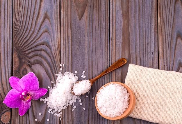Sale da bagno bianco in una ciotola di legno con un cucchiaio, sapone, tela e orchidea sul tavolo di legno