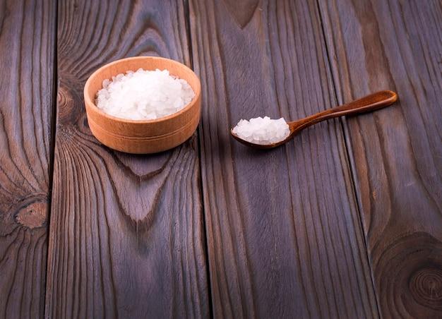Sale da bagno bianco in una ciotola di legno con un cucchiaio su un tavolo di legno