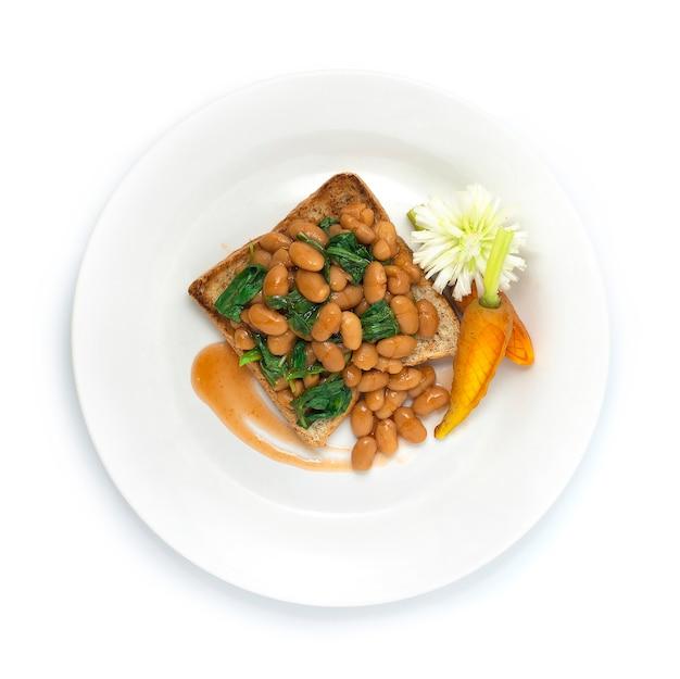 Fagioli bianchi e spinaci su pane in fibra di cottura ad alto contenuto di vitamine e proteine