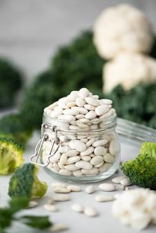 Fagioli bianchi in un barattolo di vetro con verdure verdi su un tavolo bianco