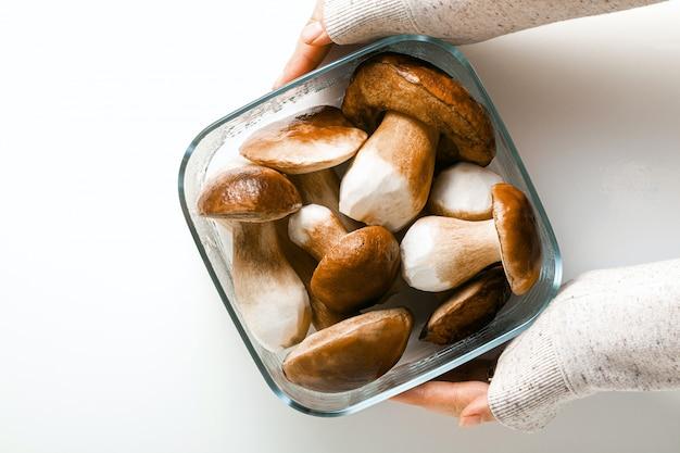 Funghi porcini grandi belli bianchi su sfondo bianco in una ciotola di vetro e mani femminili