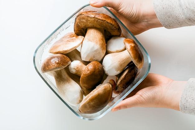 Funghi porcini grandi belli bianchi su bianco in una ciotola di vetro e mani femminili
