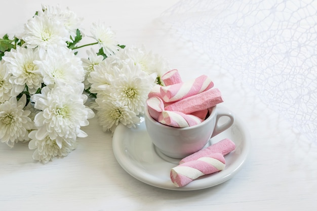 Bouquet di crisantemi bianchi belli e marshmallow in tazza su fondo bianco. bel biglietto di auguri per san valentino o festa della mamma.