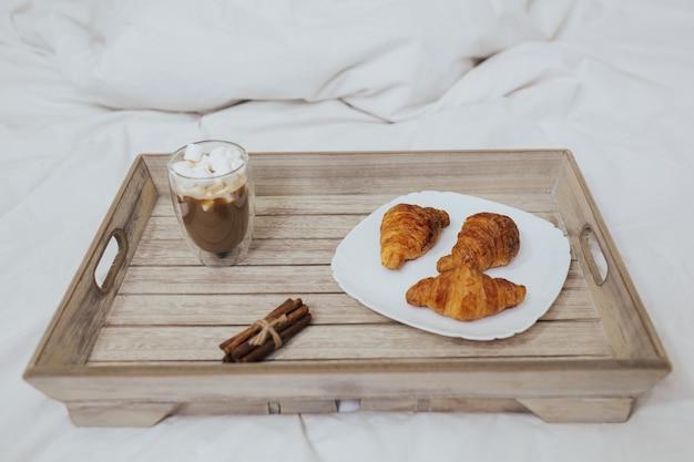 Letto bianco un vassoio con cappuccino con marshmallow e croissant