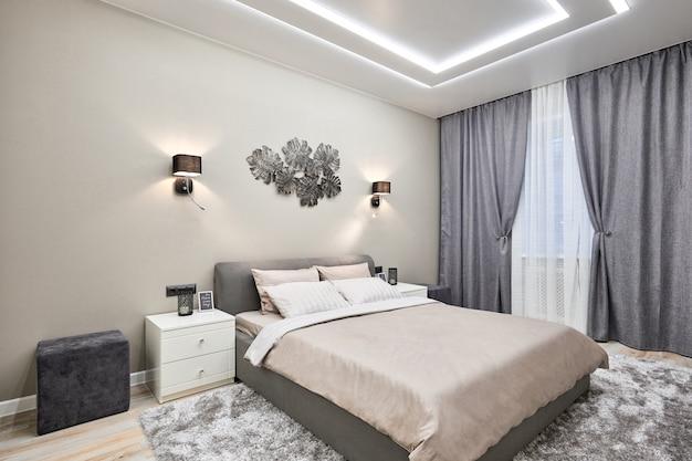 Interno camera da letto bianco con grandi finestre e ampio letto bianco