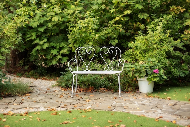 Panchina bianca nel giardino estivo per il relax