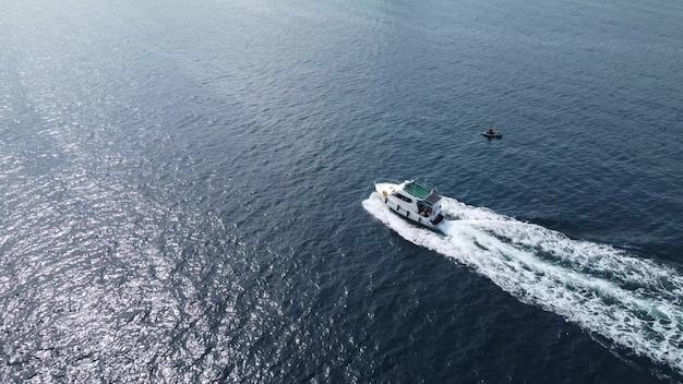 Grande movimento bianco della barca sulla vista aerea dell'acqua blu. volo su uno yacht bianco in movimento. barca a motore ad alta velocità con persone che si muovono sull'acqua di mare.