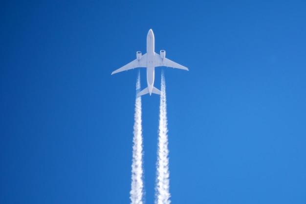 Bianco grande aereo passeggeri due motori aviazione aeroporto nuvole di scia di condensazione.