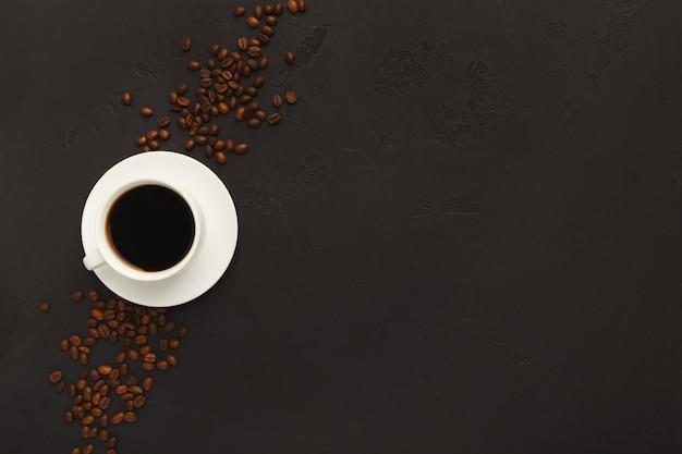 Tazza di caffè nera bianca sul piattino e fagioli arrostiti sparsi su fondo strutturato grigio, vista superiore. design minimalista per la pubblicità della caffetteria, copia spazio