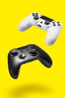 Controller di gioco bianchi e neri sulla parete gialla