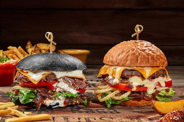 Hamburger bianchi e neri con tortino di vitello su tavola di legno con patate fritte