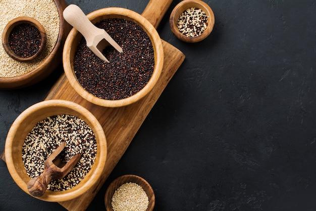 Semi di quinoa bianchi, neri e misti in una ciotola di bambù su un tavolo di pietra nera. lay piatto con copia spazio.