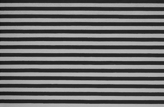 Muro di intonaco dello stucco del fondo di struttura a strisce bianche e nere
