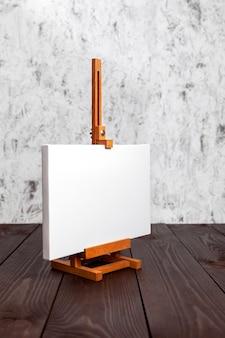 Tela bianca bianca tesa sul telaio ausiliario e un cavalletto in piedi su un tavolo di legno marrone. modello