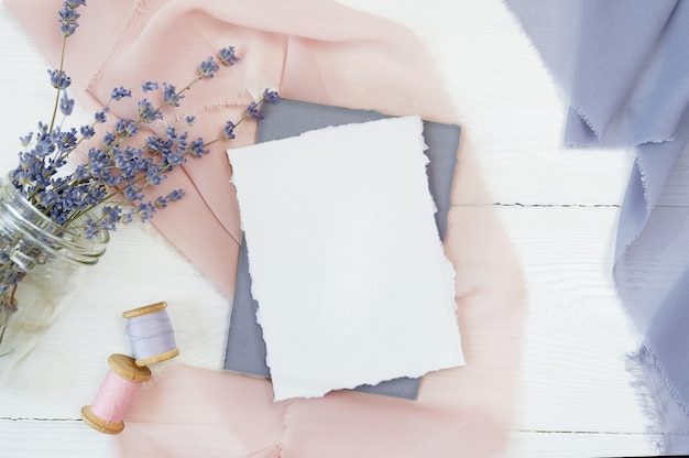 Carta bianca in bianco su un tessuto rosa e blu con fiori di lavanda