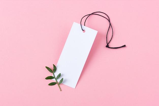 Etichetta bianca per vestiti in bianco con corda nera su sfondo rosa. piccolo ramo verde con foglie