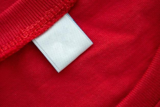 Etichetta bianca in bianco dell'etichetta dell'abbigliamento sul nuovo fondo rosso di struttura del tessuto della camicia di cotone