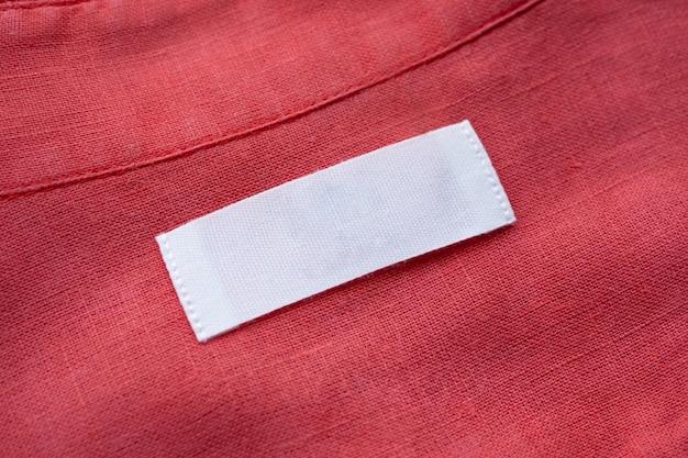Etichetta dell'etichetta dell'abbigliamento in bianco bianco sul fondo di struttura del tessuto della camicia di lino rossa