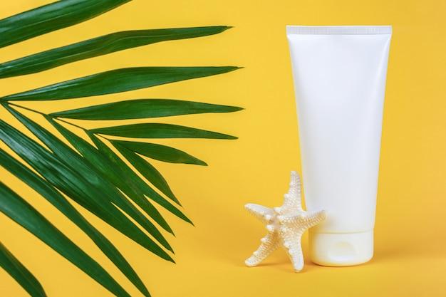 Tubo cosmetico bianco bianco con crema solare, crema solare per viso o corpo, stelle marine e palma brunch verde su sfondo giallo.