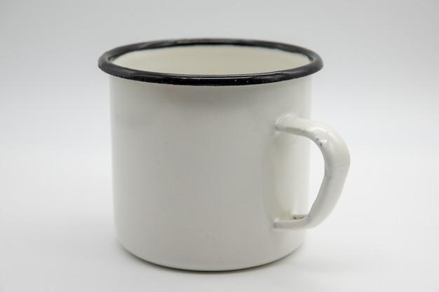 Tazza in bianco bianca dello smalto isolata su fondo bianco