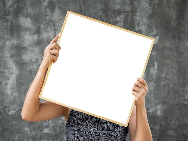 Mockup di cornice vuota bianca in cornice di legno quadrata. mani della donna che tengono lo spazio quadrato in bianco nel telaio di legno sul fondo del muro di cemento grigio di lerciume.