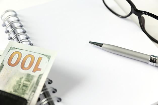Taccuino in bianco bianco con penna e occhiali d'argento. alcuni soldi e portafoglio si trovano vicino ad esso.