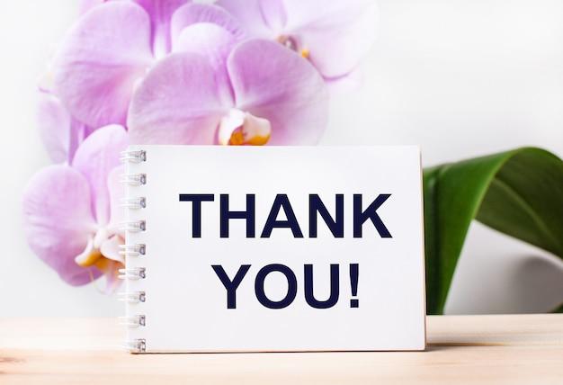 Taccuino in bianco bianco con il testo grazie sul tavolo sullo sfondo di un'orchidea rosa chiaro.