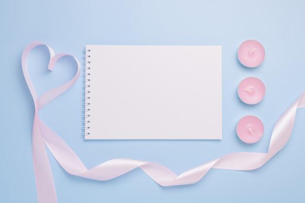 Foglio di blocco note vuoto bianco, candele e nastro a forma di cuore su sfondo blu. concetto di san valentino.