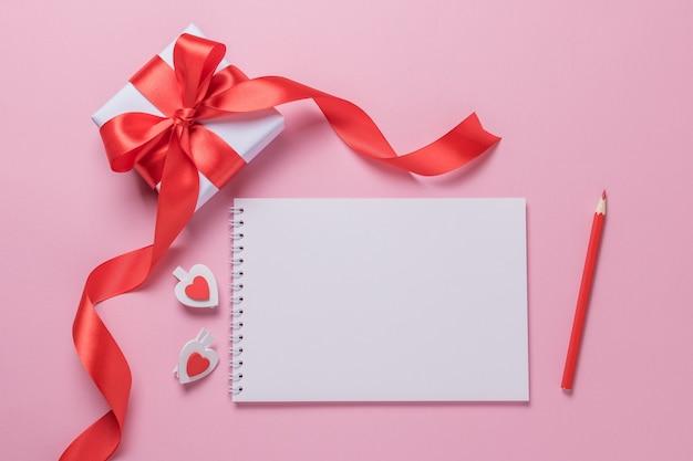 Foglio di blocco note vuoto bianco, confezione regalo e matita su uno sfondo rosa. posto per il testo. buon san valentino.