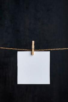 Note bianche bianche appese con mollette sulla corda. superficie nera. copia spazio. spazio per il tuo testo. cornice verticale.