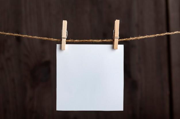 Note bianche bianche appese con mollette su corda su superficie di legno. copia spazio, . spazio per il tuo testo.