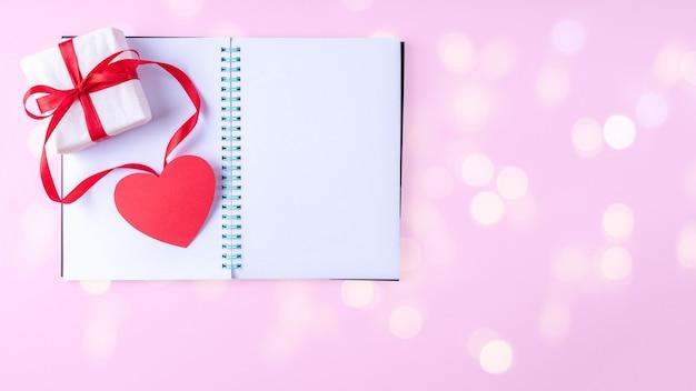 Blocco note aperto vuoto bianco, penna rossa, confezione regalo con nastro rosso e carta rosa a forma di cuore su sfondo rosa