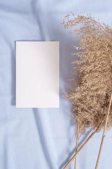 Mockup di carta di carta bianca bianca con erba secca di pampa su tessuto di colore neutro blu