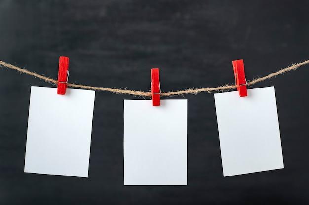 Le carte di carta bianca bianca sono appese con mollette sulla corda. superficie nera. copia spazio, .
