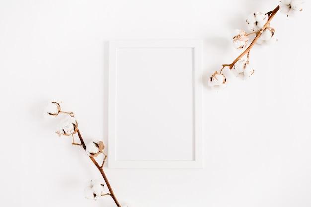 Cornice per foto in bianco bianca mock up e rami di cotone su bianco