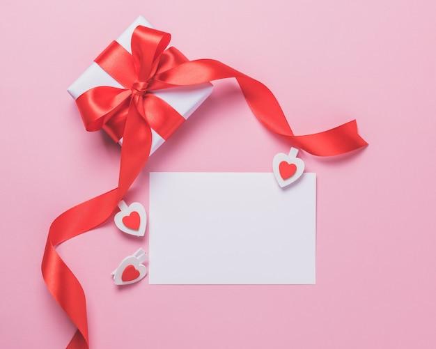 Foglio di carta bianco bianco e confezione regalo su sfondo rosa. concetto di san valentino.
