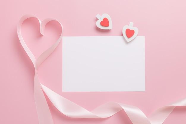 Foglio di carta bianco bianco e nastro rosa a forma di cuore su sfondo rosa. concetto di san valentino.