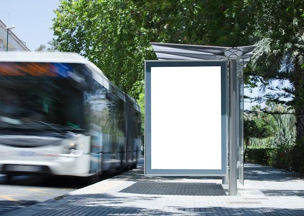 Tabellone per le affissioni verticale vuoto bianco alla fermata dell'autobus sulla strada della città sullo sfondo di autobus e ro