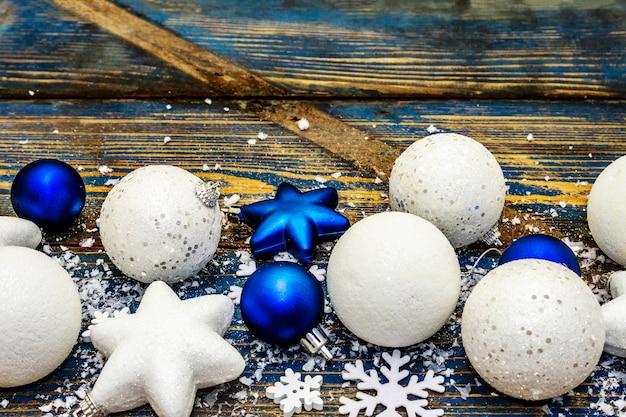 Palle di natale bianche e blu e stelle, fiocchi di neve e glitter sparsi con neve artificiale. tavole di legno d'epoca nei toni del blu, copia dello spazio