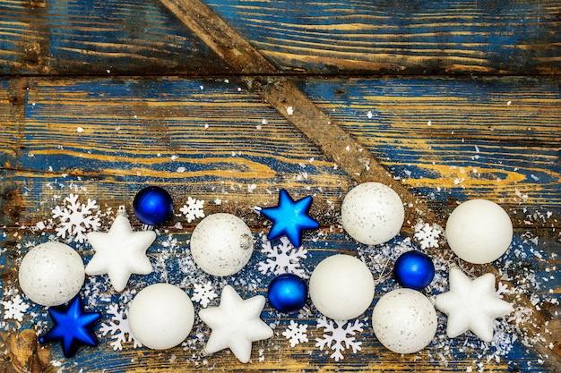Palle di natale bianche e blu e stelle, fiocchi di neve e glitter sparsi con neve artificiale. tavole di legno vintage nei toni del blu, vista dall'alto