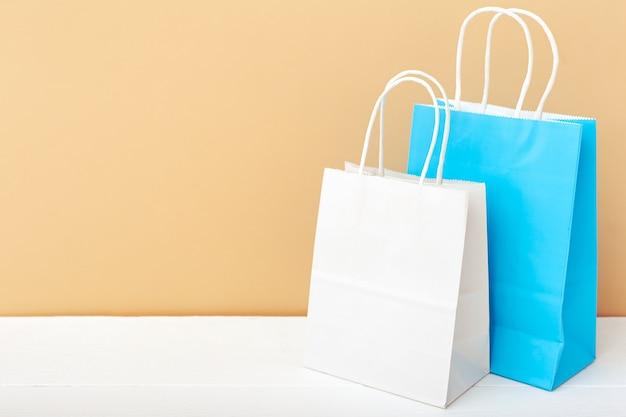 Sacchetti di carta artigianale blu bianchi. shopping mockup insacca i pacchetti di carta sullo spazio beige della copia della tabella bianca.