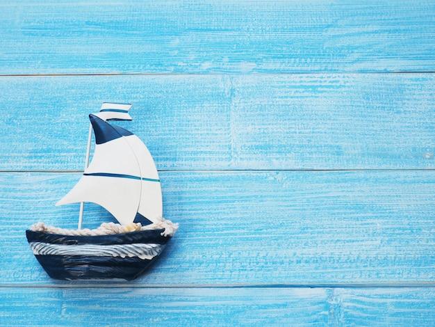 Barca a vela bianca e blu su fondo di legno blu con lo spazio della copia. vacanze estive sul concetto di spiaggia.