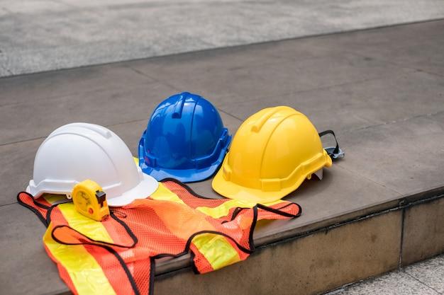 Casco di sicurezza rigido bianco, blu, giallo sul gilet con nastro di misurazione