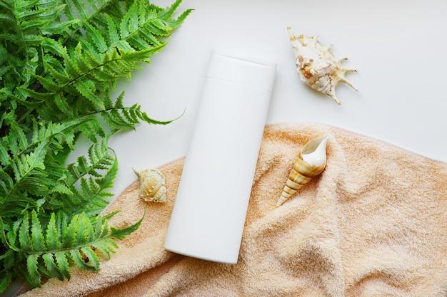 Bottiglia bianca di shampoo senza marca su un asciugamano beige con conchiglie e alghe. prodotti per la cura dei capelli con elementi marini.