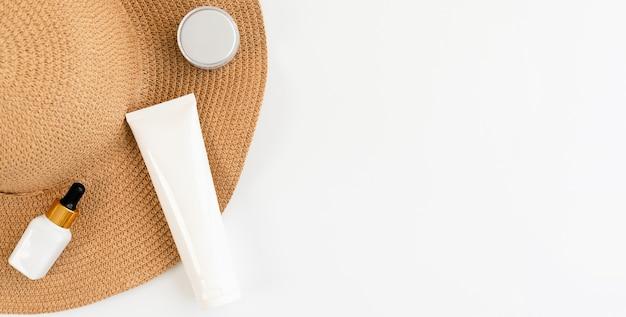Crema di bottiglia bianca sul cappello, mockup del marchio di prodotti di bellezza. vista dall'alto sul muro bianco.