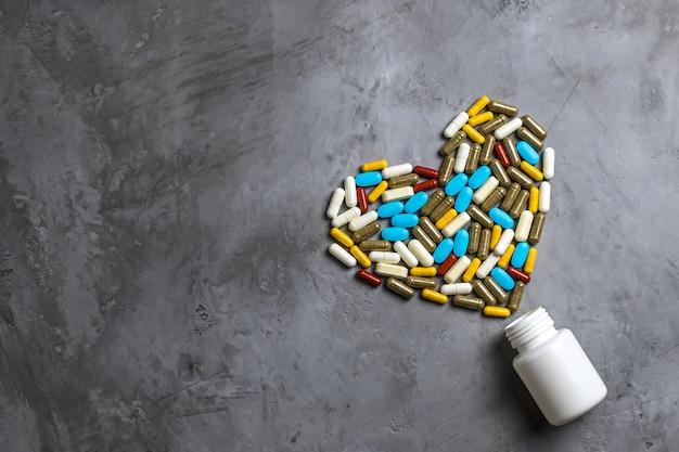 Bottiglia bianca e pillole multicolori a forma di cuore. sfondo grigio cemento. concetto di prodotti farmaceutici, medicinali, farmaci per il trattamento delle malattie cardiovascolari. disposizione piatta, vista dall'alto