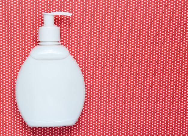 Bottiglia bianca di shampoo su rosso creativo a pois, vista dall'alto
